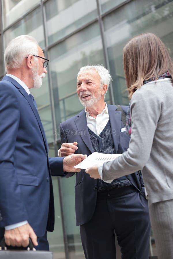 Petit groupe d'hommes d'affaires se réunissant dans la rue en dehors d'un immeuble de bureaux, regardant des rapports de ventes photos stock
