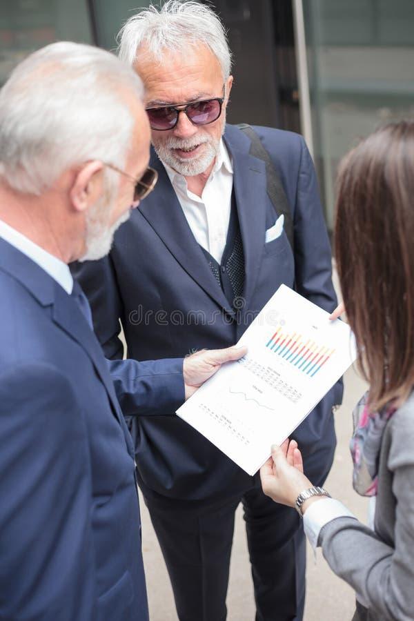 Petit groupe d'hommes d'affaires se réunissant dans la rue en dehors d'un immeuble de bureaux, regardant des rapports de ventes image stock