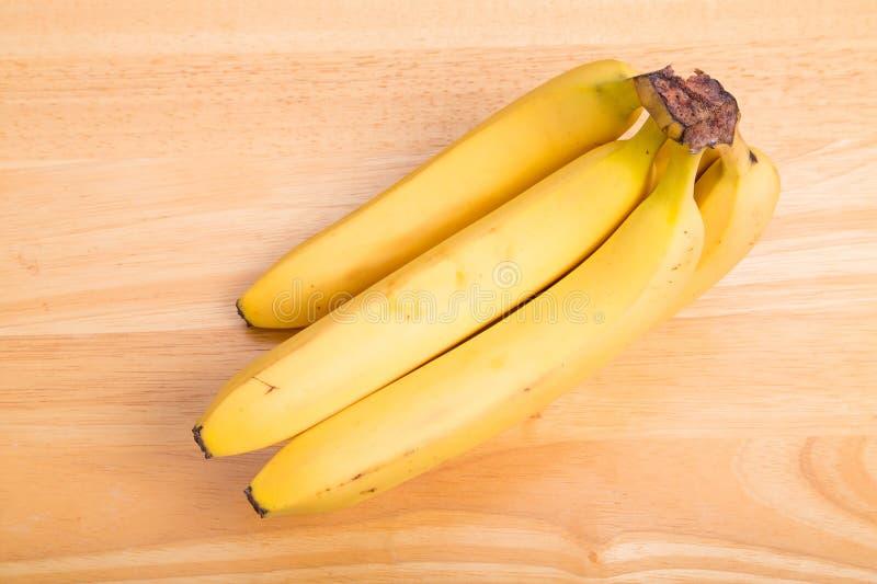 Petit groupe de bananes jaunes sur le Tableau en bois photos stock