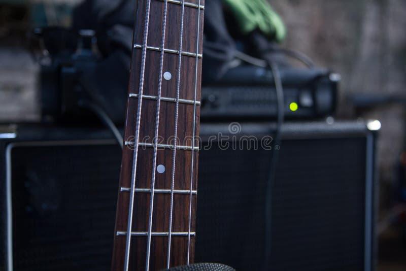 petit groupe horizontal du panneau de frette d'une guitare basse sur le fond d'ampère photographie stock