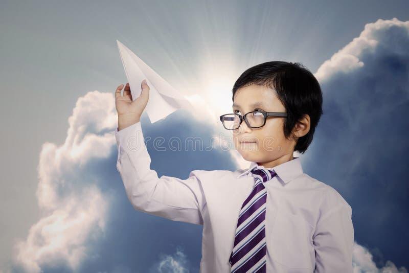 Petit homme d'affaires jetant un avion de papier photo stock