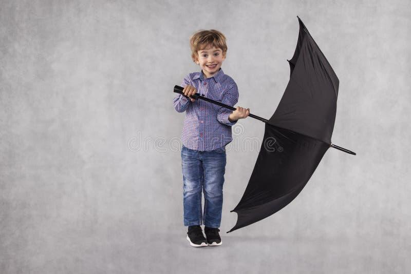 Petit homme d'affaires tenant un parapluie dans des mains image stock