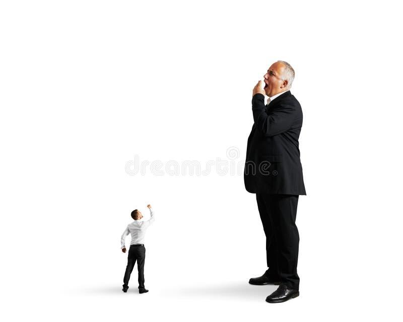 Petit homme montrant le poing au grand homme d'affaires ennuyé photos libres de droits
