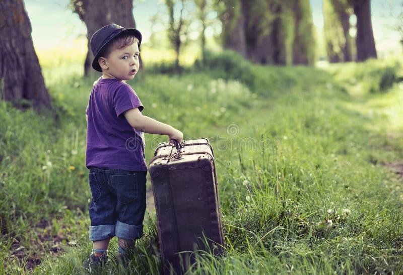 Petit homme partant à la maison avec le bagage énorme photos stock