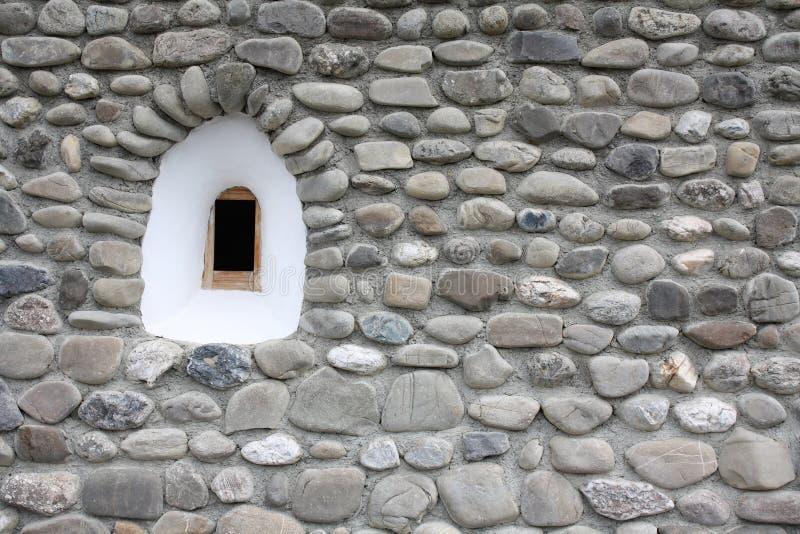 Petit hublot médiéval à l'intérieur d'un mur en pierre image libre de droits