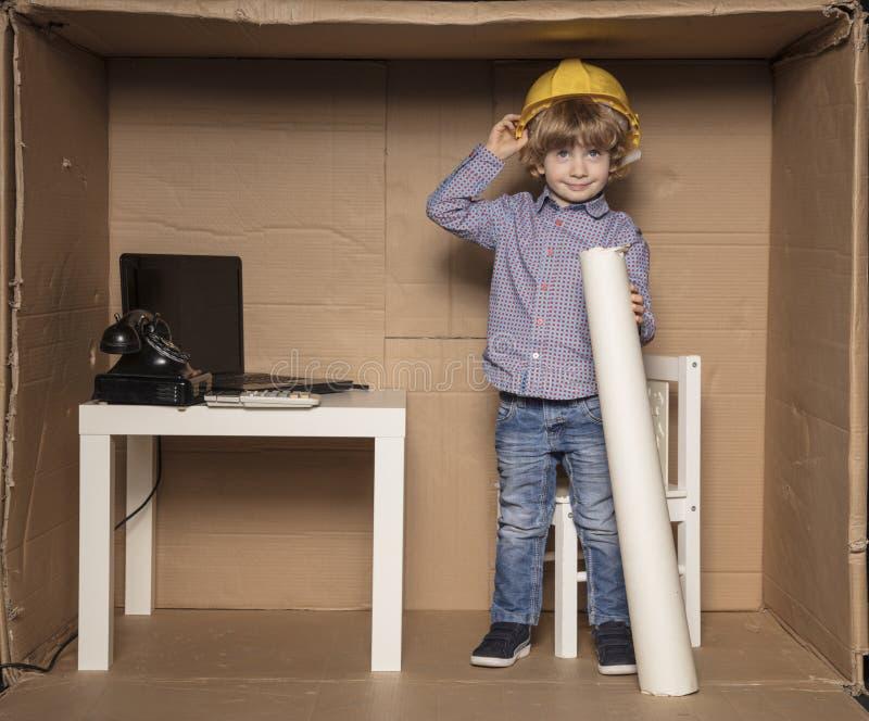 Petit ingénieur heureux dans son petit bureau photographie stock libre de droits