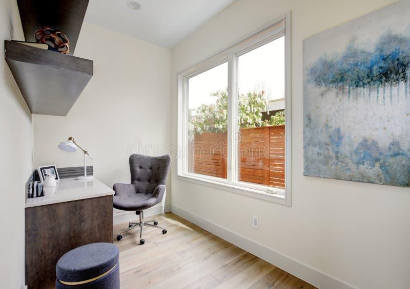 Petit intérieur léger de siège social avec le bureau faisant le coin et une chaise photos libres de droits