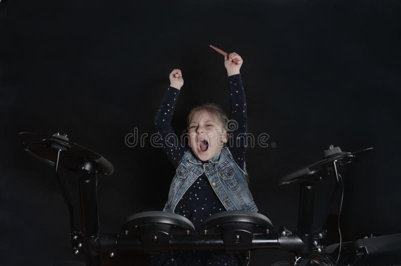 Petit jeu caucasien de batteur de fille le kit elettronic de tambour photographie stock