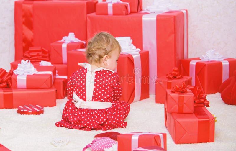 Petit jeu de b?b? pr?s de la pile des bo?te-cadeau rouges envelopp?s Mon premier No?l Partager la joie de premier No?l de b?b? av photo libre de droits