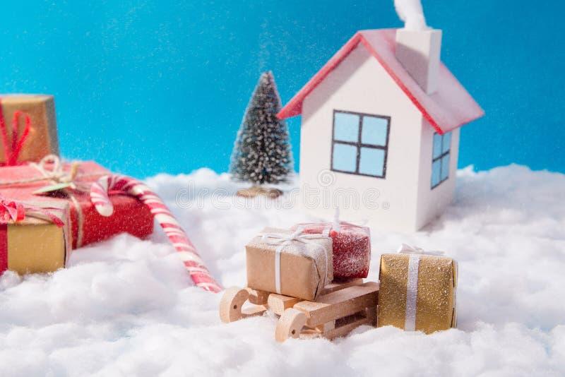 Petit jouet santa claus confort blanc maison chaleureuse confortable avec concept de fumée livrer des gifbox roux sur des traînea photographie stock