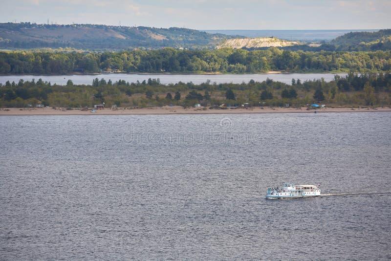 Petit karabl de plaisir flottant sur la rivière dans la perspective de la côte avec des arbres et des montagnes photo stock