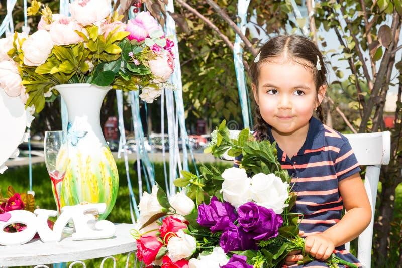 Petit kazakh adorable, fille asiatique d'enfant sur le fond de nature de vert d'été Concept et enfant de fleur image stock
