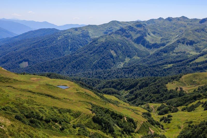 Petit lac de montagne et prés alpins verts en montagnes de Caucase photographie stock