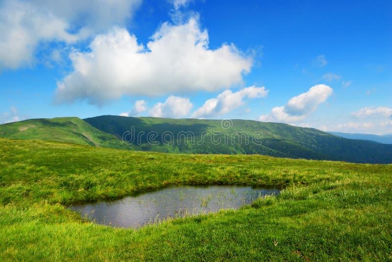 Petit lac sur le pré et les nuages photographie stock