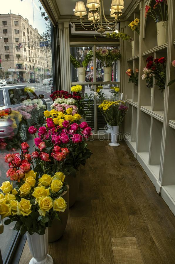 Petit magasin de ville avec de beaux bouquets vivants des roses lumineuses dans des pots de fleur blanche à la fenêtre image libre de droits