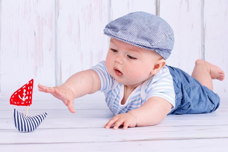 Petit marin heureux de bébé jouant avec un bateau photographie stock