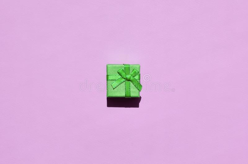 Petit mensonge vert de boîte-cadeau sur le fond de texture du papier rose en pastel à la mode de couleur de mode photos stock