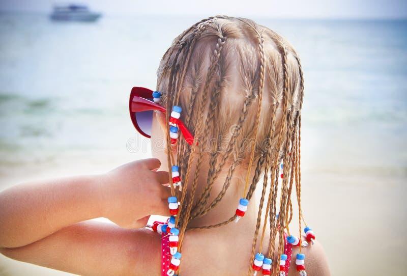Petit mignon avec la fille de dreadlocks sur la plage tropicale image libre de droits