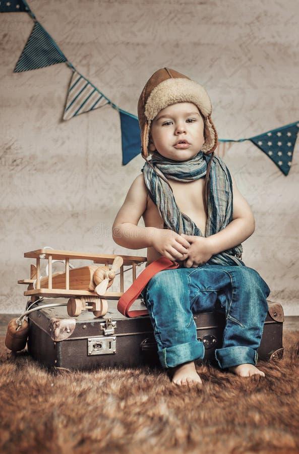 Petit, mignon pilote avec un avion en bois images stock