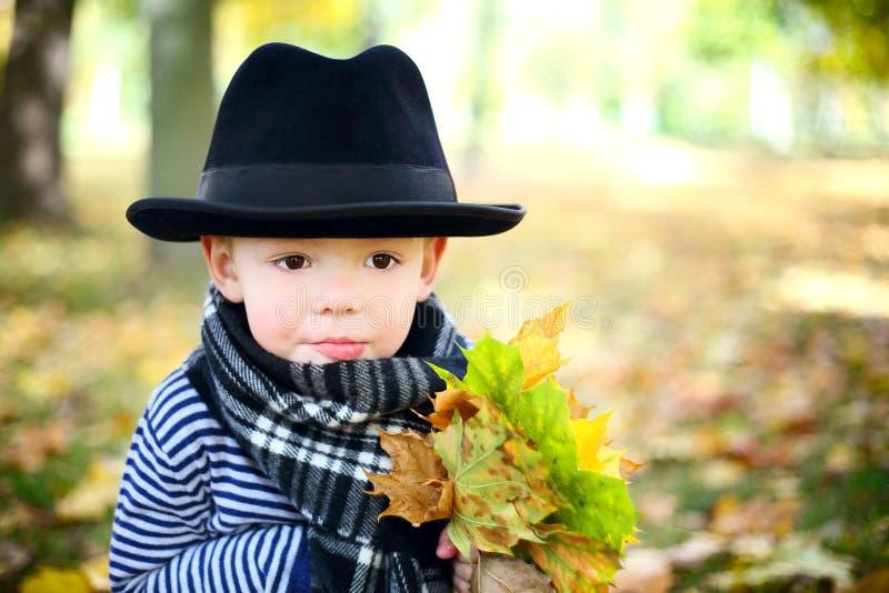 Petit monsieur mignon dans un chapeau noir en stationnement d'automne photographie stock