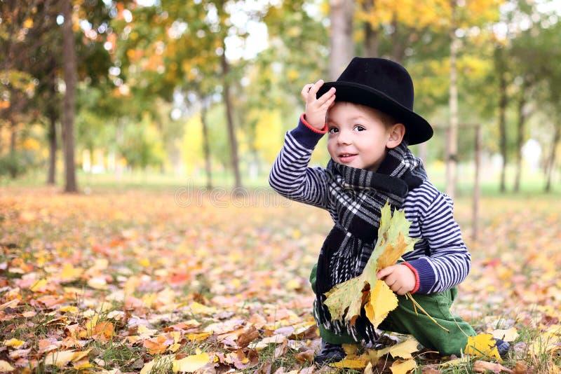 Petit monsieur mignon dans un chapeau noir en stationnement d'automne photo stock