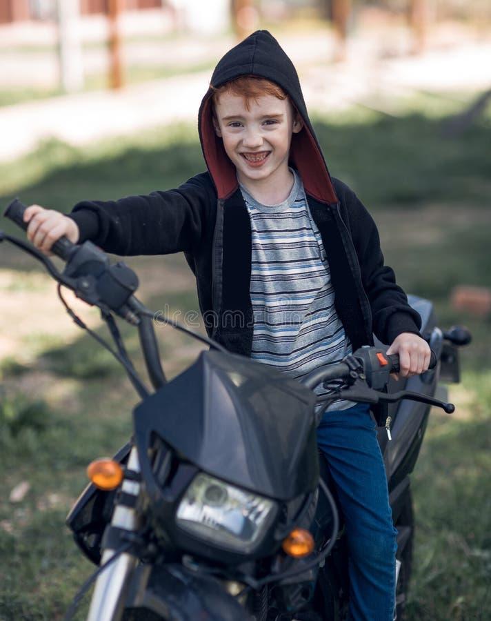 Petit motard de sourire montant une moto photo libre de droits