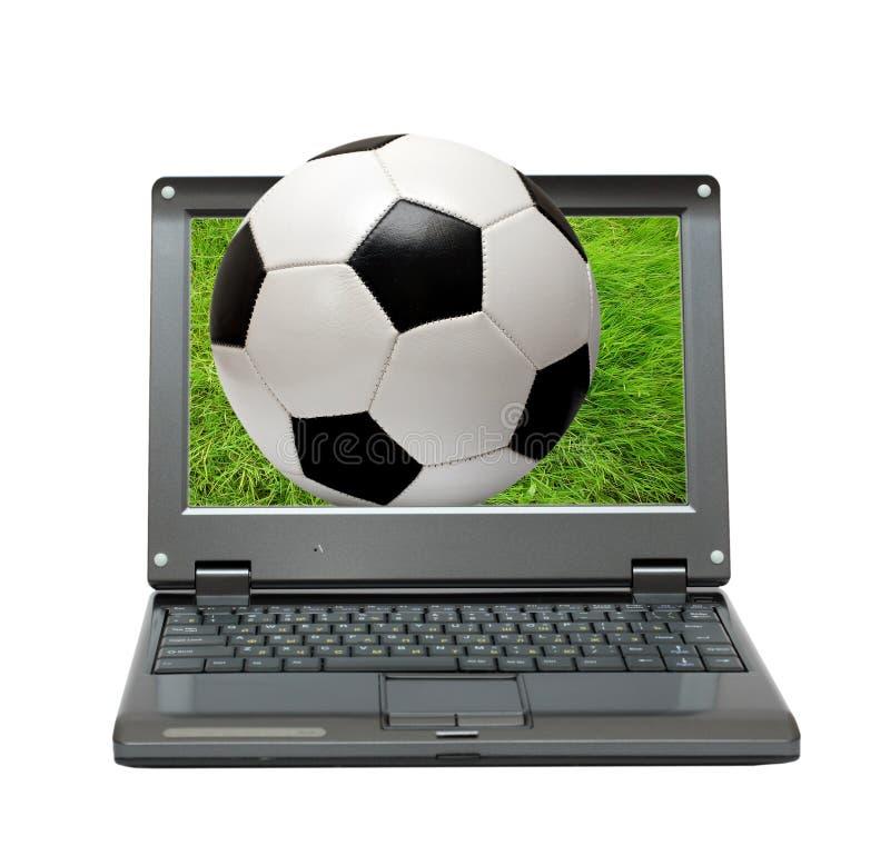 Petit ordinateur portatif avec la bille du football du football photographie stock