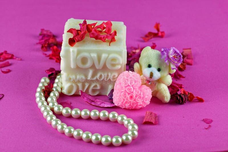 Petit ours de nounours avec la boîte d'amour Fond rose photographie stock