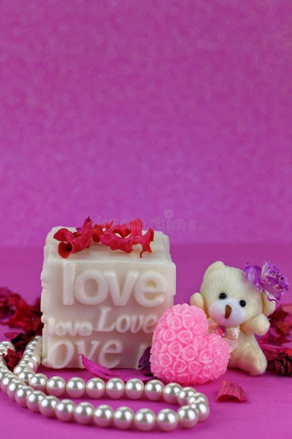 Petit ours de nounours avec la boîte d'amour Fond rose photo stock