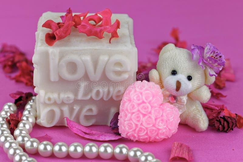 Petit ours de nounours avec la boîte d'amour Fond rose images stock