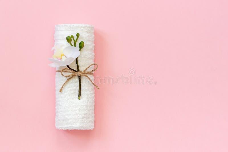Petit pain blanc de serviette attaché avec la corde avec le brin de la fleur d'orchidée sur le fond de papier rose Calibre de l'e images stock