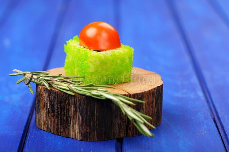 Petit pain d'imagination avec la tomate et le caviar vert sur le support en bois avec r photos stock