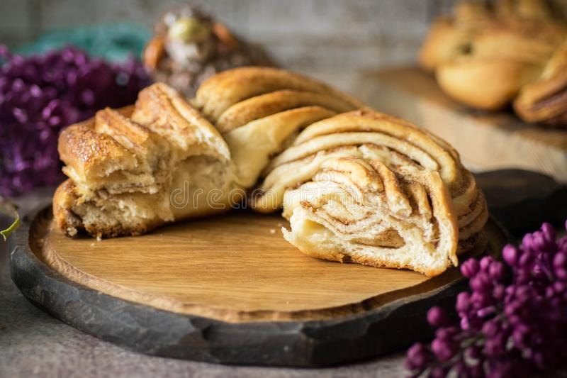 Petit pain de cannelle tressé doux sur le beau fond en bois images stock