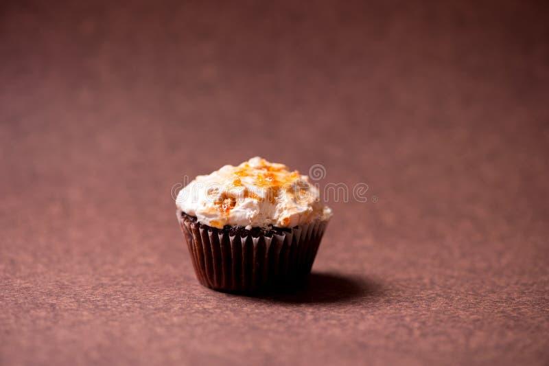 Petit pain de chocolat avec l'écrimage de crème de noisette d'isolement sur le brun photographie stock libre de droits