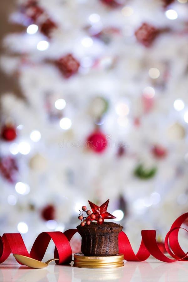 Petit pain de chocolat, décoré de l'étoile rouge, de la cuillère d'or et du fond defocused de lumières de Noël Concept de dessert photographie stock