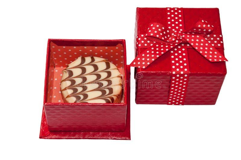 Petit pain de chocolat dans le boîte-cadeau rouge avec l'arc photos stock