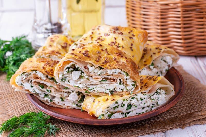 Petit pain de Lavash avec le fromage blanc et verts d'un plat photo stock