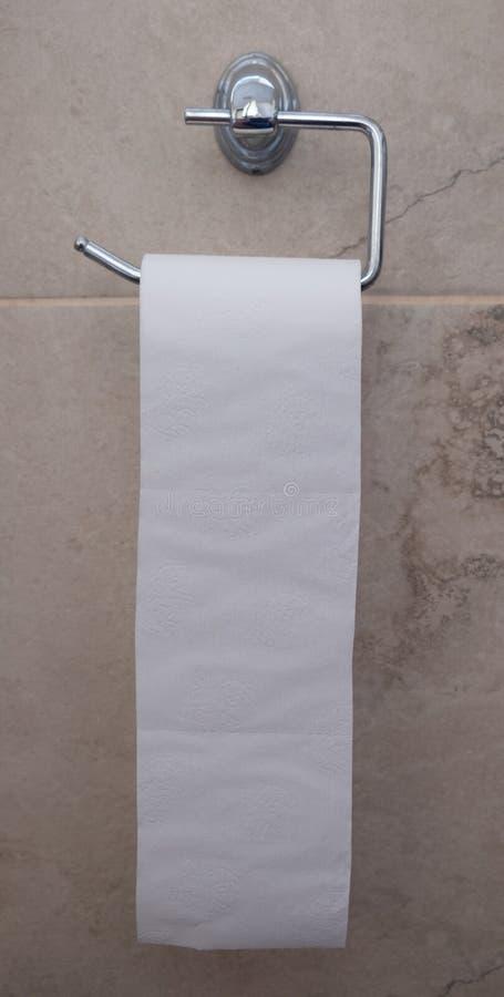 Petit pain de papier hygiénique accrochant sur le mur photo stock