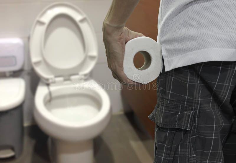 Petit pain de papier hygi?nique de participation de main et ?crire la toilette photos stock