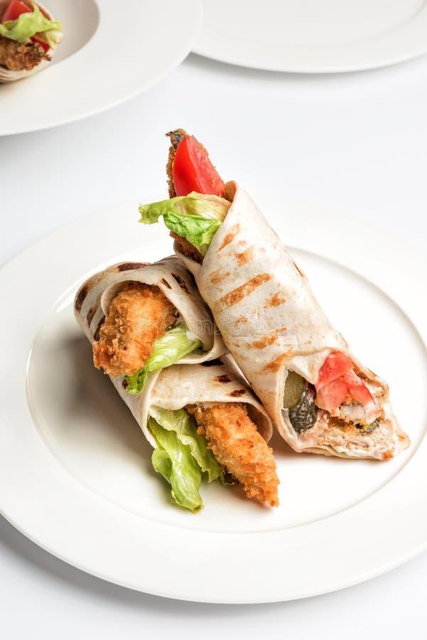 Petit pain de sandwich à tortilla avec les poissons et les légumes frits du plat image stock