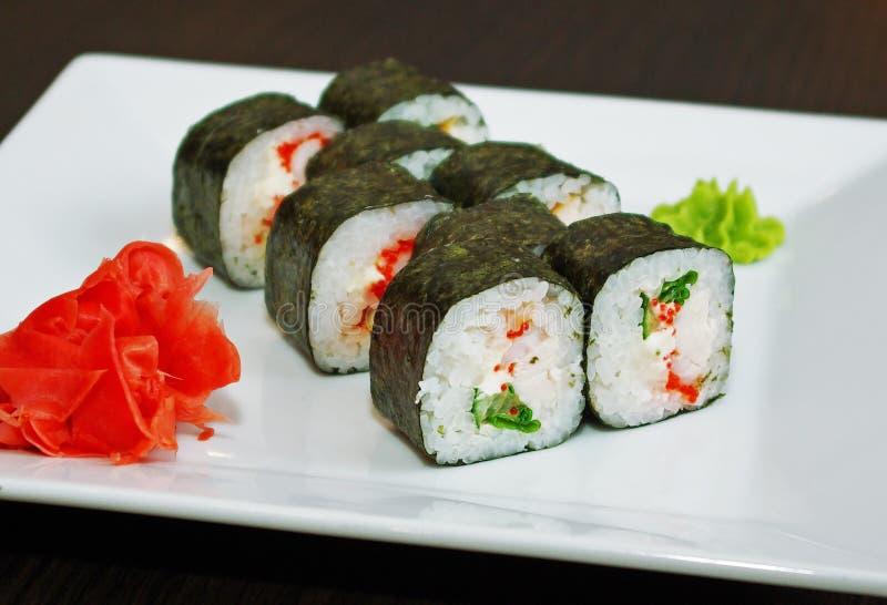 Petit pain de sushi avec le fromage fondu, la chair de crabe et les oeufs de poissons de vol image libre de droits