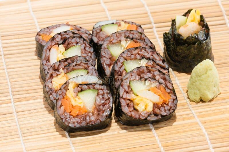 Petit pain de sushi avec le légume et le riz de côte à l'intérieur près du wasabi photographie stock libre de droits