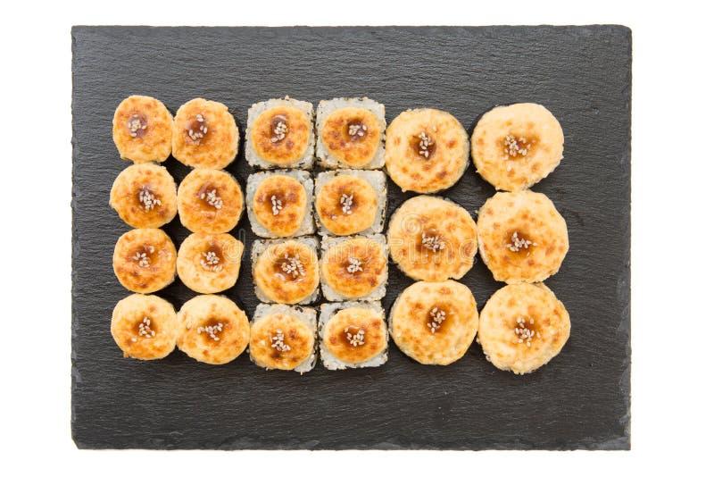 Petit pain de sushi frit chaud avec l'anguille fumée, la crevette, le fromage et l'avocat sur le fond noir Menu de sushi Nourritu photographie stock libre de droits