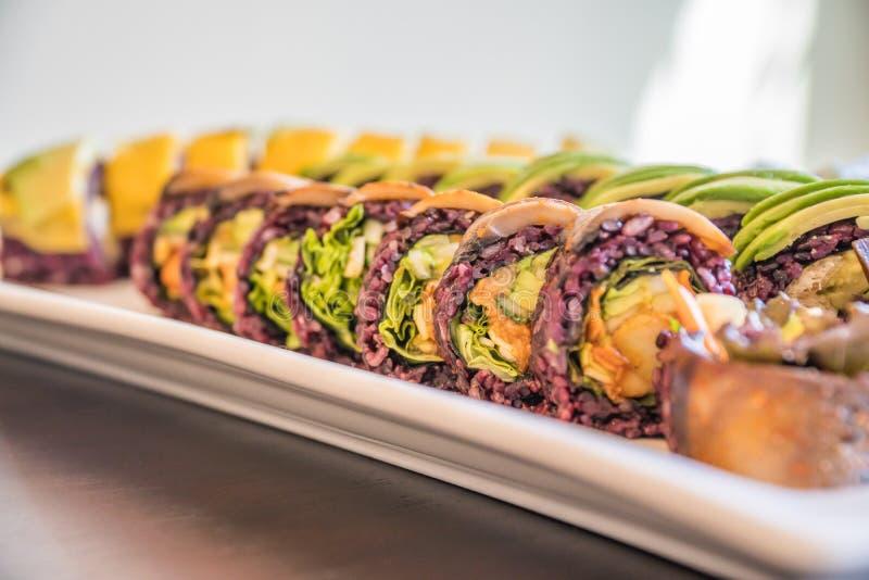Petit pain de sushi pourpre de riz avec la mangue et l'avocat pour un repas de sushi de vegan photos stock