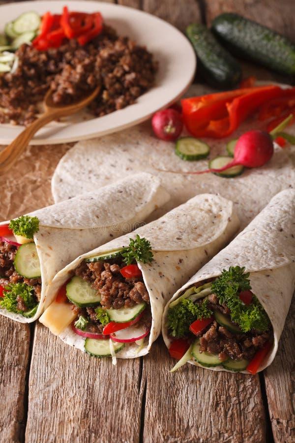 Petit pain de tortilla avec du boeuf et des légumes plan rapproché et ingrédients photographie stock