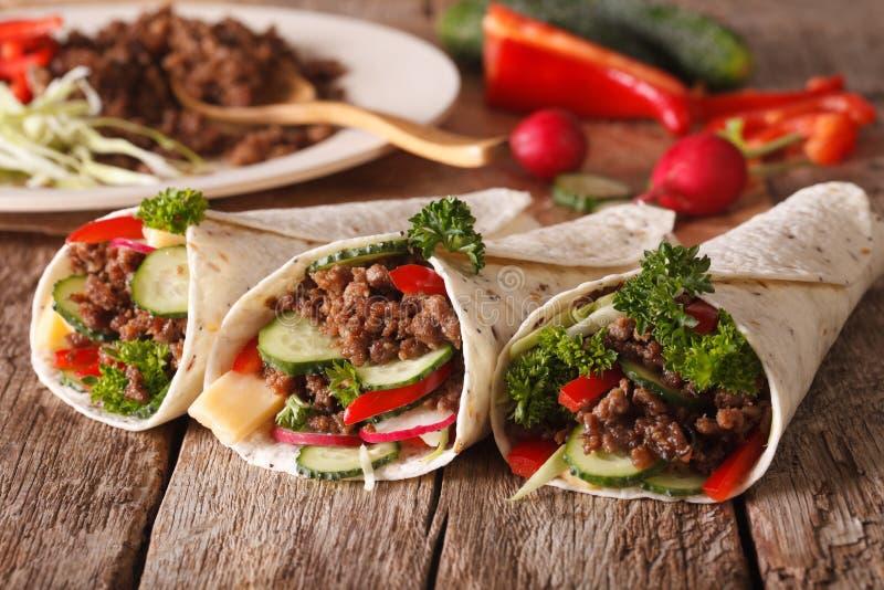 Petit pain de tortilla avec du boeuf et des légumes plan rapproché et ingrédients photo libre de droits