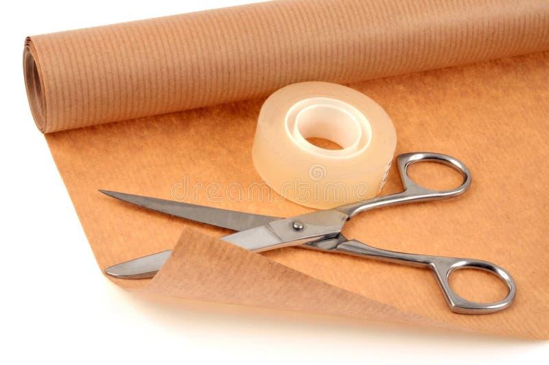 Petit pain et ciseaux adhésifs sur le papier d'emballage photographie stock libre de droits