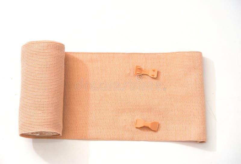 Petit pain et talonneur élastiques oranges de bandage sur le fond blanc photo libre de droits