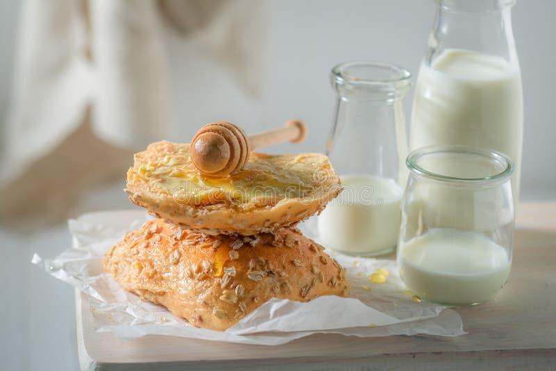 Petit pain fait maison avec du miel et le lait pendant le matin photos libres de droits
