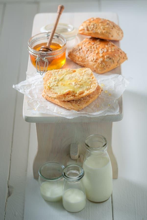 Petit pain fait maison avec du miel et le lait pour le petit déjeuner photo stock